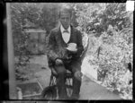 Man holding cup and saucer, seated in garden.  Pho...
