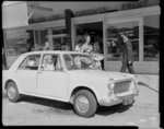 Child in parked Morris Minor at Naenae 20/1/65, ph...