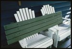 Two white painted garden chairs set on a deck besi...
