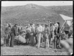 Group of gum diggers watching sacks of kauri gum b...